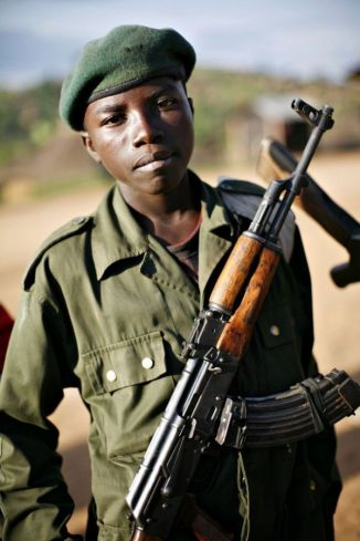 A child soldier stands at the front line in eastern Congo